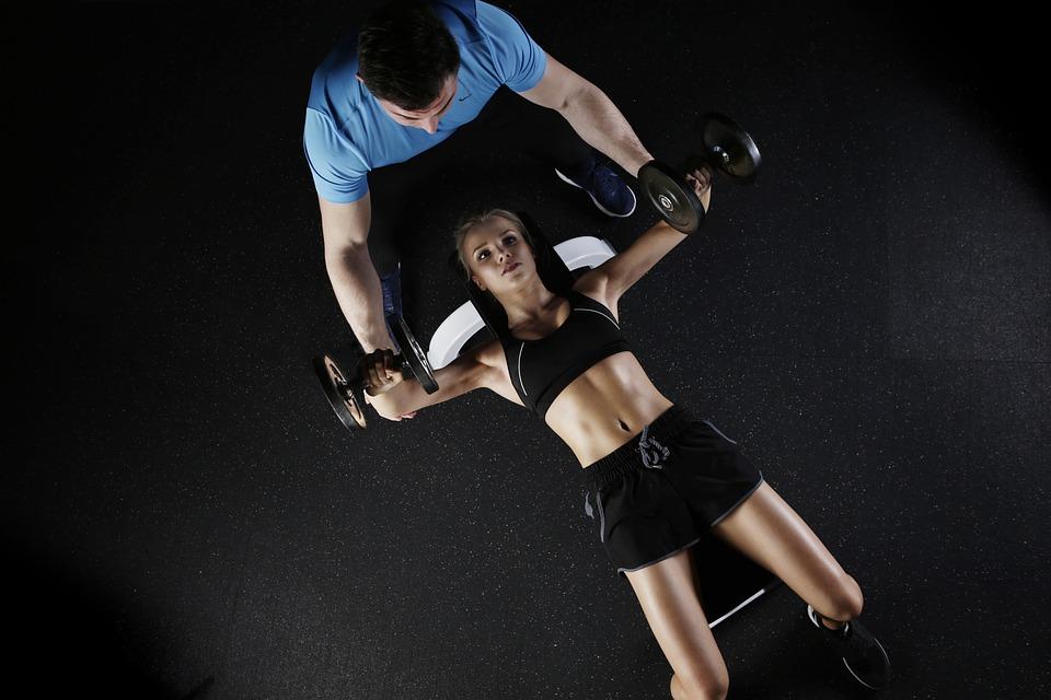 Fitnes žena vežba uz instruktora fitnesa